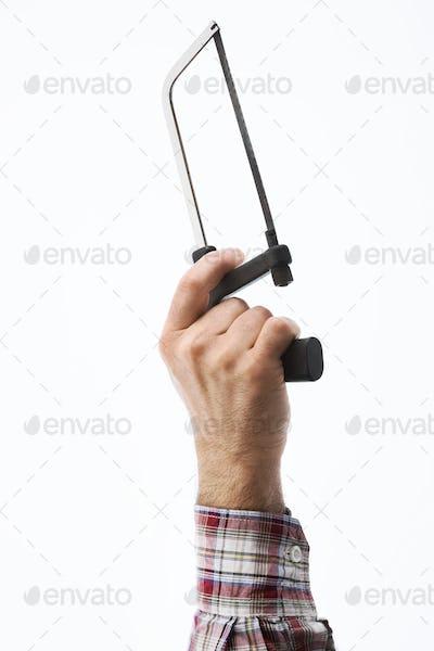 Hand holding an hacksaw