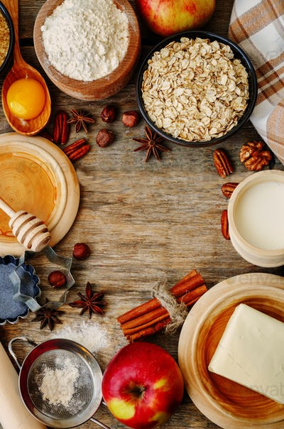 baking wood background with apples, nuts, honey, flour and butte
