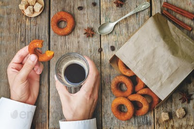 man holding glass of coffee and pumpkin donut.