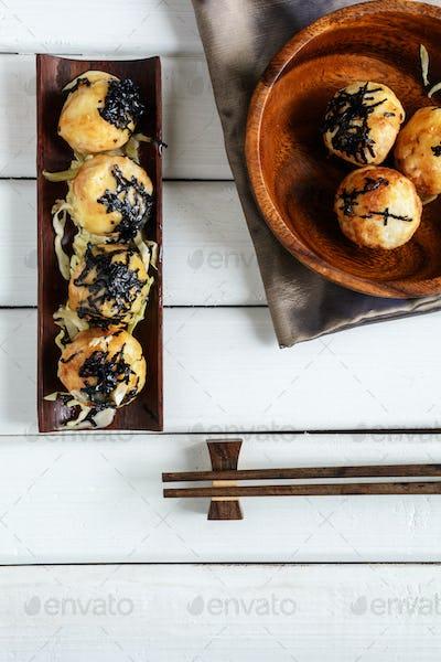Takoyaki on wooden table with chopsticks, Japanese food