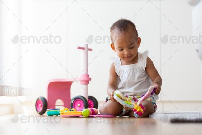 Portrait of little African American little girl sitting on the f