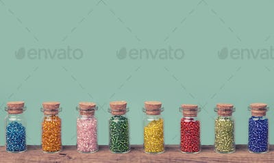 Colorful glass beads in a small bottles