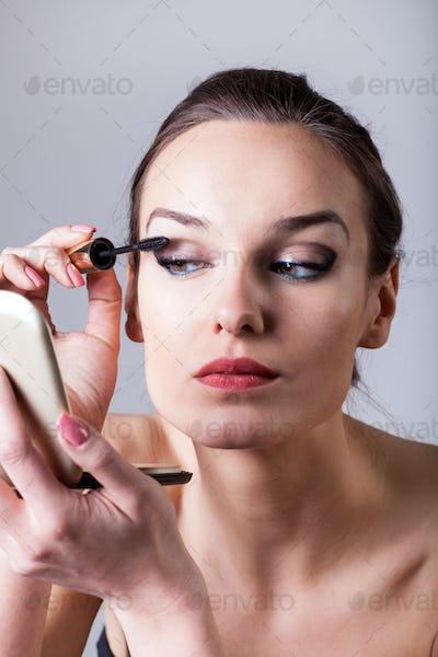 Woman painting eyelashes using mascara