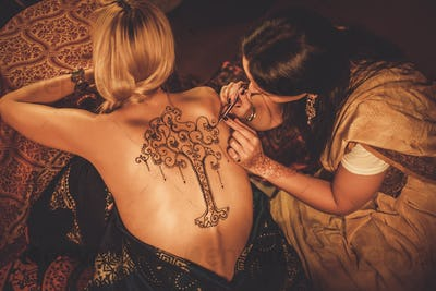 Drawing process of henna menhdi ornament on woman's back
