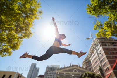 Athletic woman leaping in the city