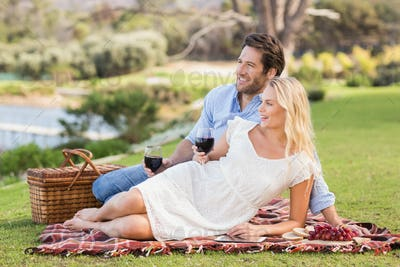 Couple on date holding red wine glasses lying on a blanket