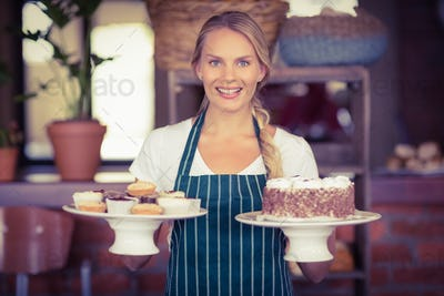 Waitress holding a chocolate cake and cupcakes at the coffee shop