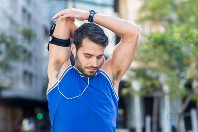 An handsome athlete listening to music on a sunny day