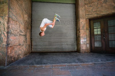 Extreme athlete doing a front flip in front of a building in the city