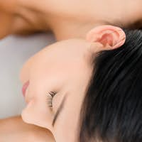 Pretty brunette enjoying a massage at camera at the health spa