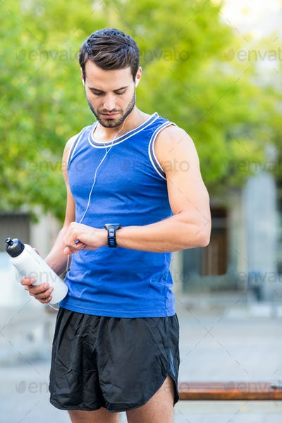 An handsome athlete holding a bottle on a sunny day