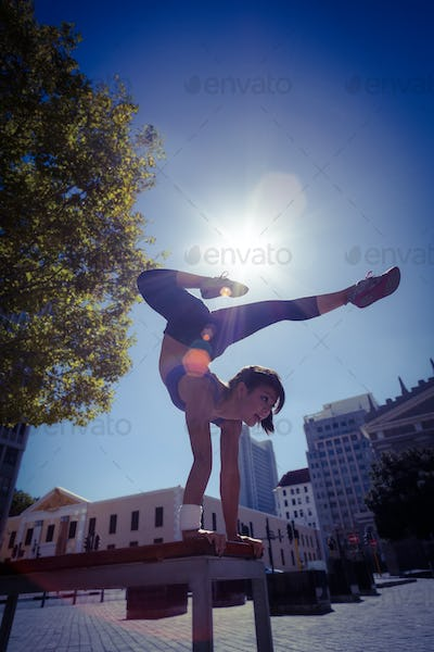 Athletic woman performing handstand on bench in the city