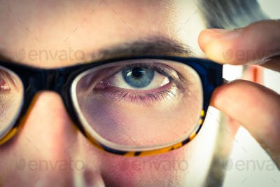 Handsome hipster touching his glasses on vignette background