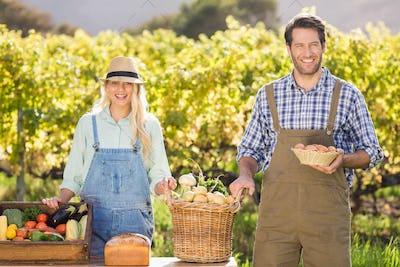 Portrait of a happy farmer couple presenting their local food