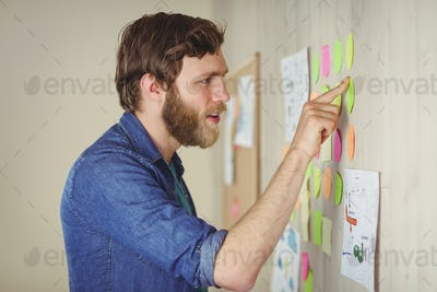 Bearded hipster looking at brainstorm wall in his office