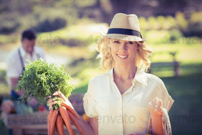 Portrait of a blonde woman holding a bunch of carrots
