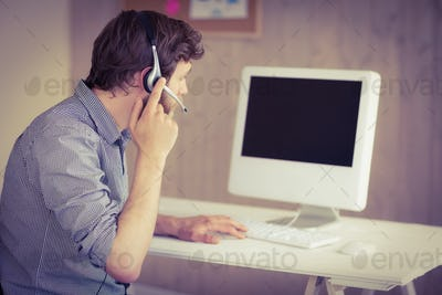Bearded hipster working at desk with headset in his office