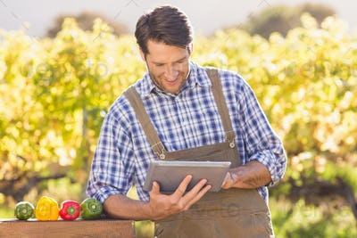 Smiling farmer using a digital tablet in the countryside