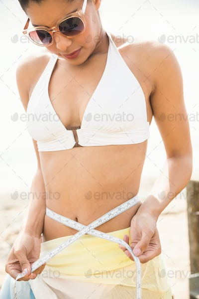 Pretty woman in bikini measuring her waist at the beach