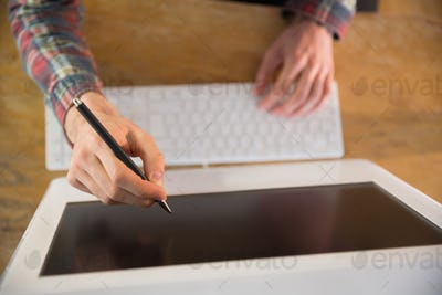 Businessman pointing at computer with pen in his office