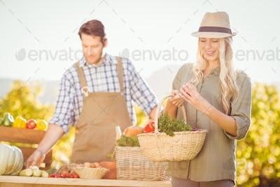 Blonde customer holding a vegetables basket at the local market