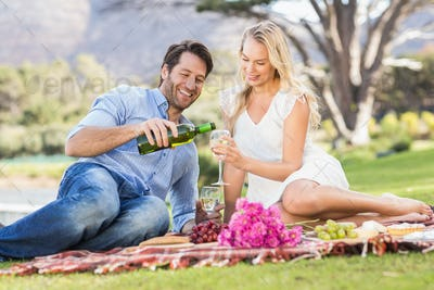 Cute couple on date drinking wine while lying on the grass