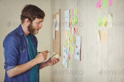 Bearded hipster getting an idea in his office