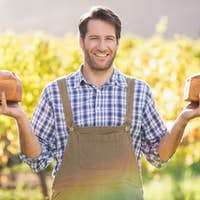 Portrait of a smiling farmer holding two tasty breads