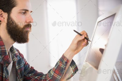 Hipster businessman pointing at computer with pen in his office