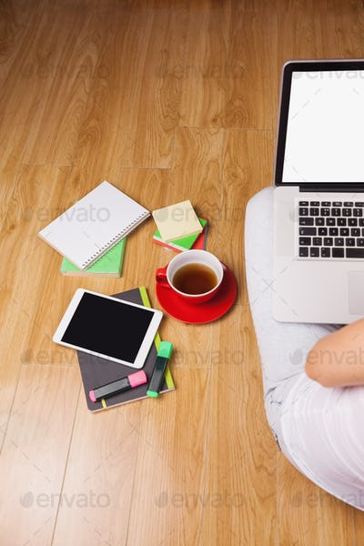 Overhead shot of laptop, tablet, coffee and headphones on a desk