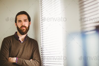Hipster businessman leaning beside window in his office