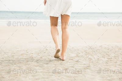 Stylish woman walking on the sand at the beach