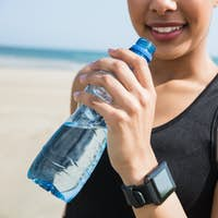 Fit woman wearing smart watch at the beach