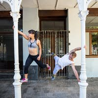 Happy couple doing parkour in the city on a sunny day