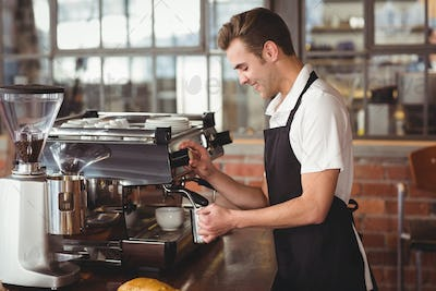 Smiling barista steaming milk at coffee machine at coffee shop