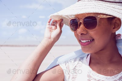 Stylish woman in hat and sunglasses at the beach