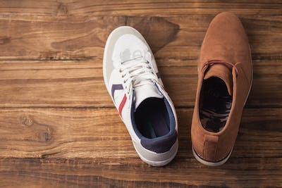 Casual and dressy mens shoes on wooden table