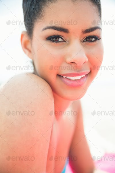 Smiling woman sunbathing on towel at the beach