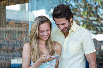 Smiling couple looking at smartphone at shopping mall