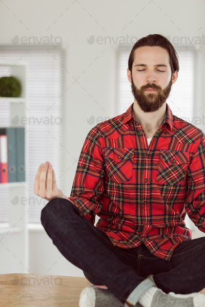 Hipster businessman meditating at his desk in his office