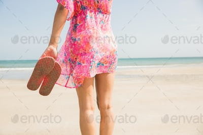 Stylish woman standing on the sand at the beach