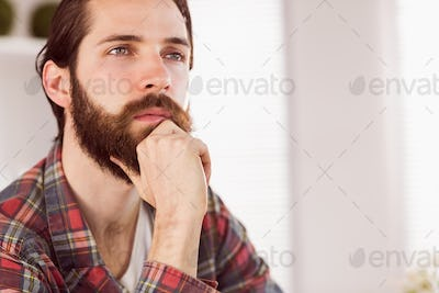 Hipster businessman thinking at his desk in his office