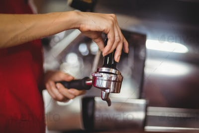 Close up view of a barista pressing coffee at the coffee shop
