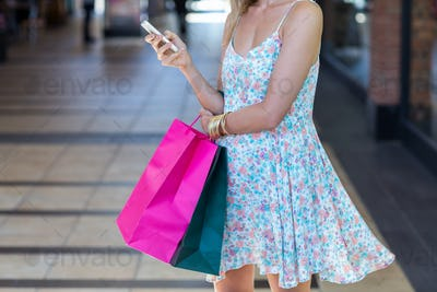 Woman walking with shopping bags and holding smartphone at shopping mall