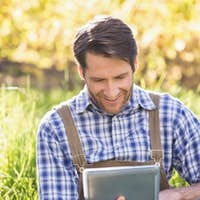 Smiling farmer using a digital tablet sitting on the grass