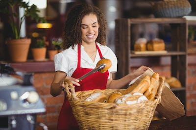 Smiling waitress picking up bread from a basket at the coffee shop