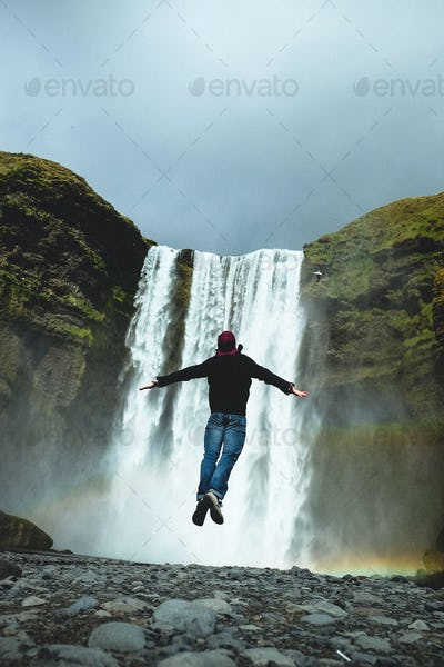 man jumping in front of waterfall
