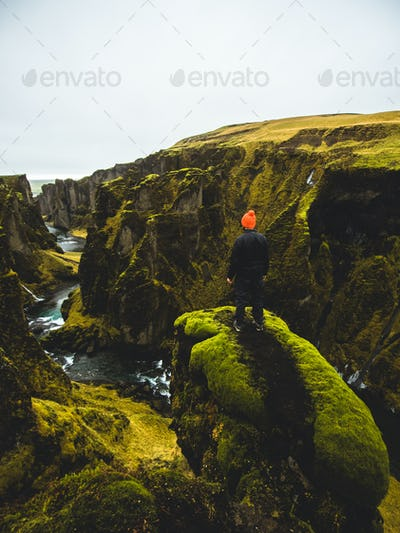 Man standing on a ledge at a green canyon in Iceland