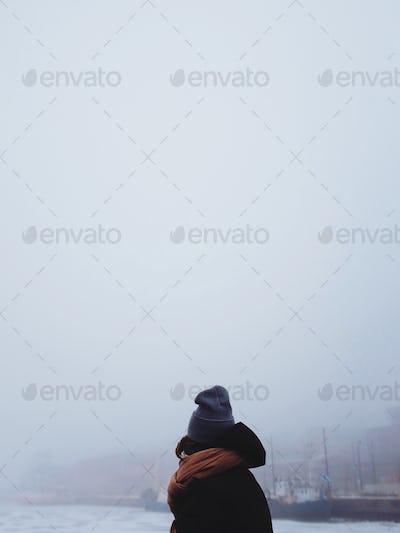 Woman framed agains a foggy sea view