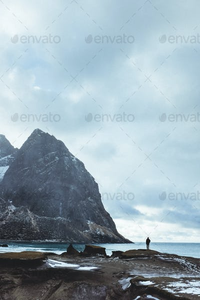 Fjord beach with man silhouetted agains the sky and sea